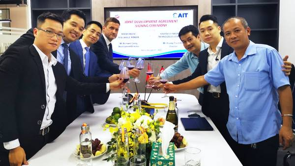 Mainstream's Development Director in Vietnam, Bernard Casey, centre left, and AIT Director Hoang Thanh Hai, centre right, lead their teams in toasting the new joint venture agreement at the signing ceremony in Hanoi - Credit: Mainstream Renewable Power